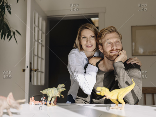 Smiling couple sitting at table at home with toy dinosaurs