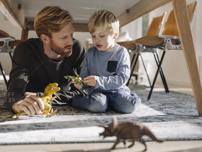 Father and son playing with dinosaur figures under the table at home