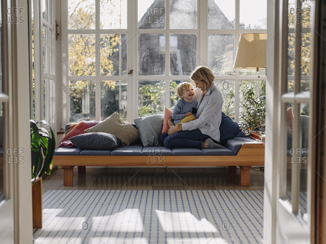 Happy mother and son in sunroom at home