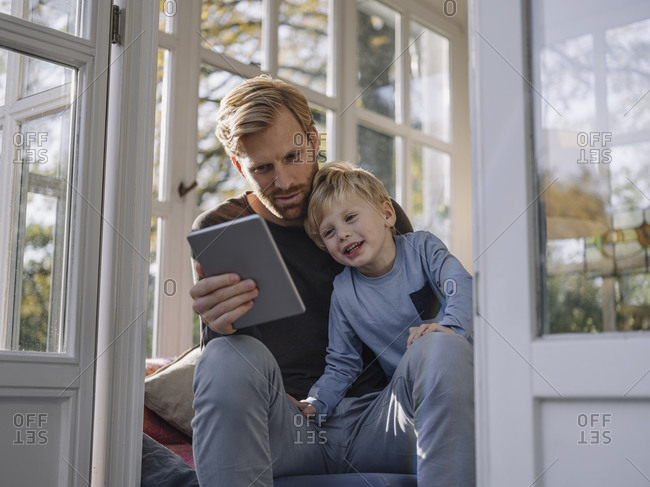 Father and son using tablet in sunroom at home