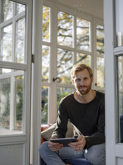 Portrait of man using tablet in sunroom at home