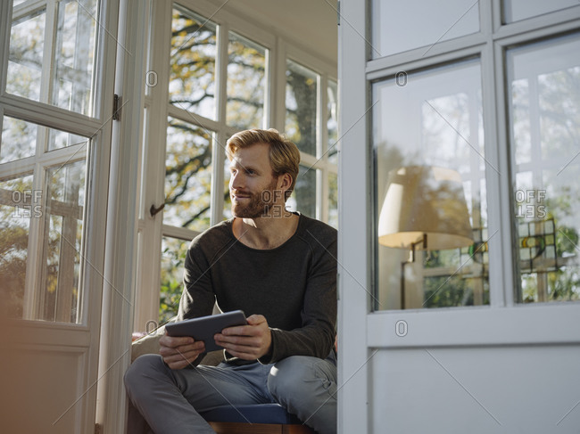 Man using tablet in sunroom at home