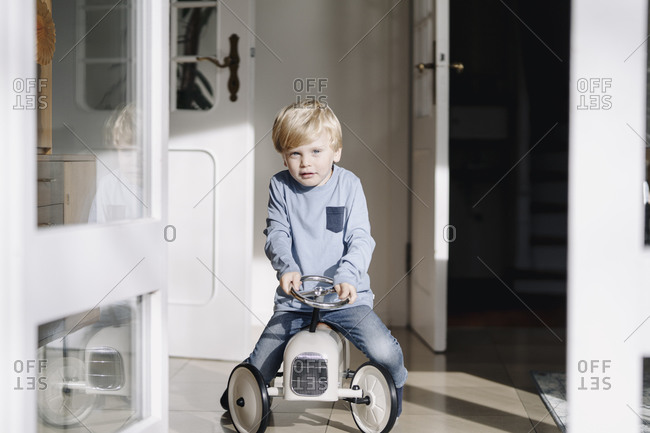 Portrait of boy playing with toy car at home