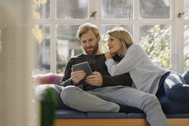 Man with wife using tablet in sunroom at home
