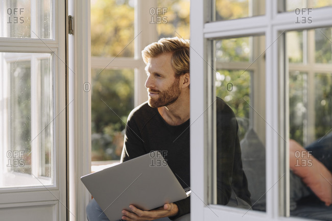 Man using laptop in sunroom at home