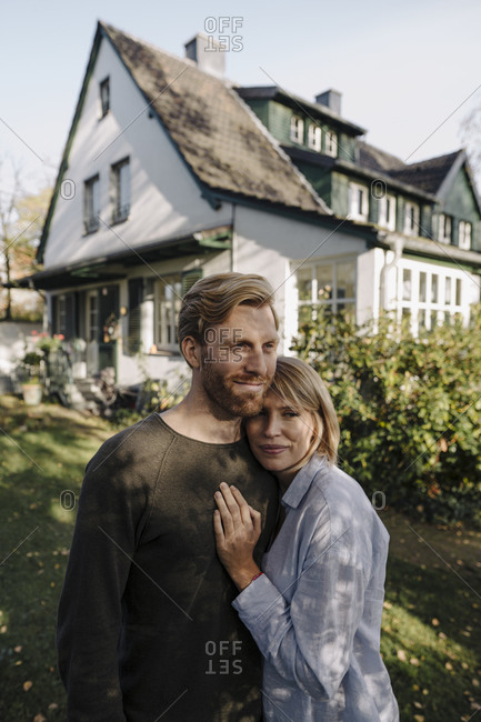 Smiling couple standing in front of their home