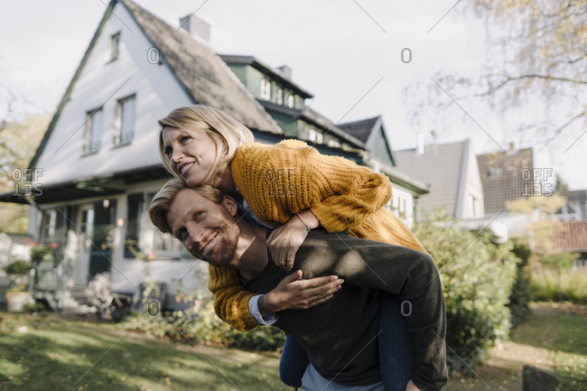 Man giving his wife a piggyback ride in garden