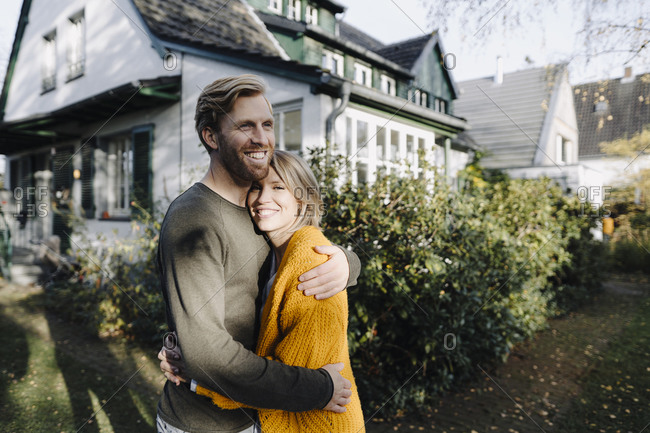 Happy couple embracing in front of their home