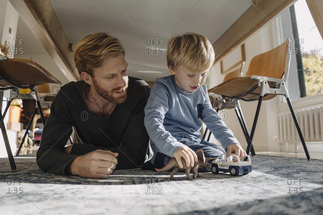 Father and son playing with dinosaur figure and toy car under the table at home