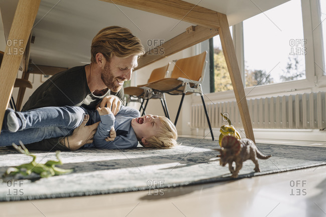 Father and son playing under the table at home