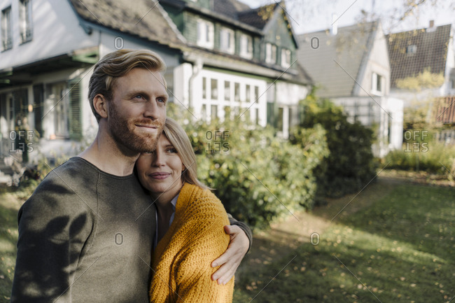 Smiling couple embracing in garden of their home