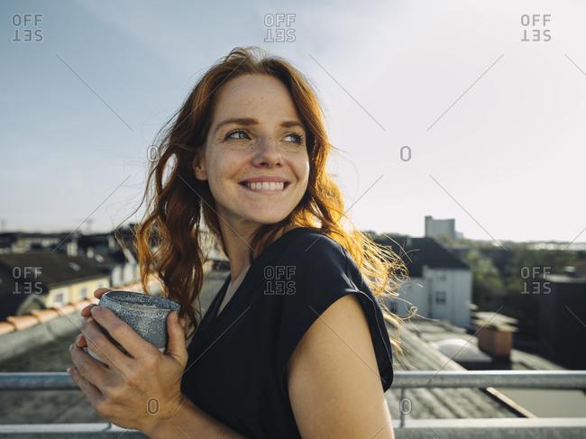 Smiling redheaded woman having a coffee break on rooftop terrace