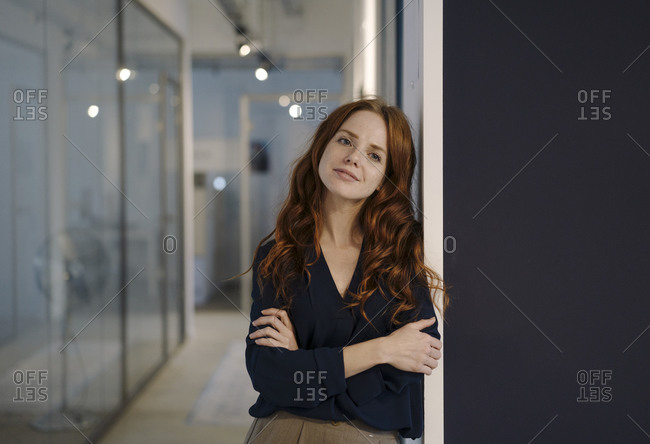 Portrait of smiling redheaded woman on office floor
