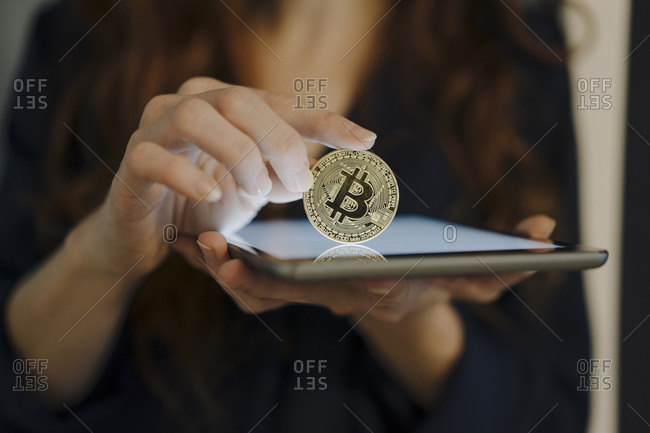 Close-up of woman holding bitcoin and tablet