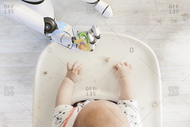Robot hand giving pacifier to baby boy sitting in high chair playing with bread crumps- top view