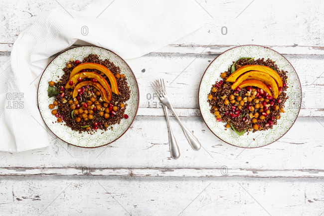Studio shot of salad of red quinoa with baked pumpkin- chickpeas- pomegranate- basil- walnuts and pumpkin seeds