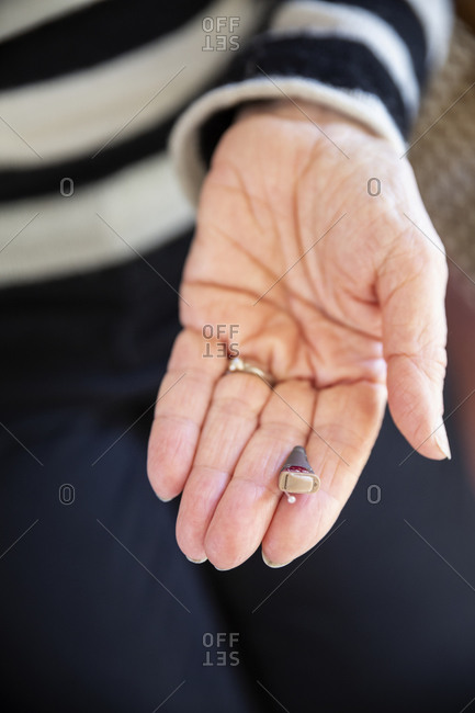 Senior woman's hand with modern hearing aid
