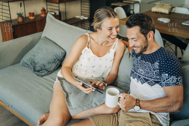 Happy relaxed couple sitting on couch in living room sharing a tablet