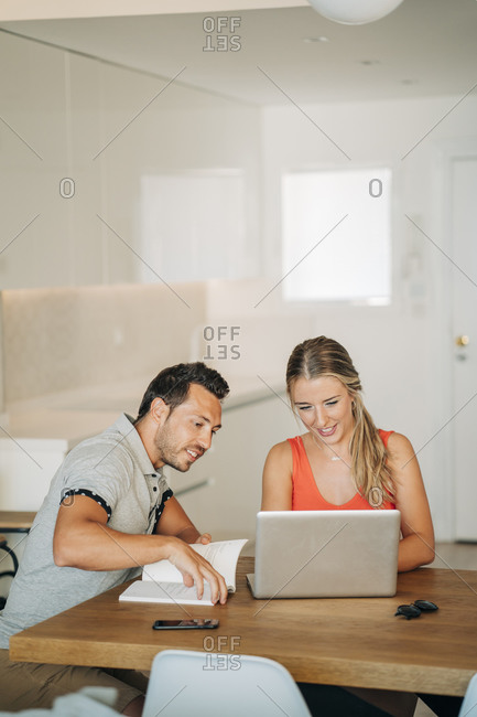 Happy couple sitting at table with laptop and book