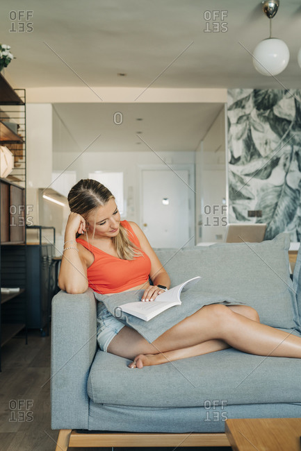 Relaxed woman sitting on couch in living room reading book