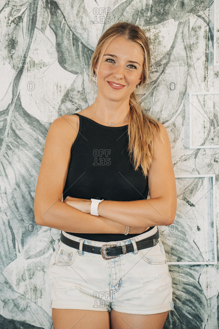 Portrait of smiling woman standing at a wall