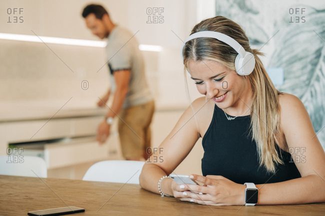 Smiling woman sitting at table with headphones and smartphone