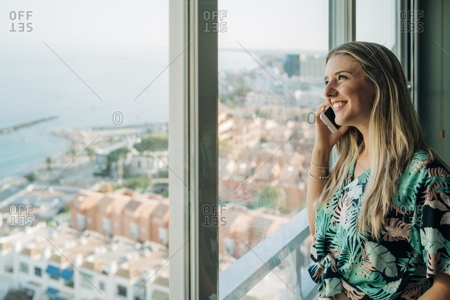 Smiling woman on the phone at the window in coastal town
