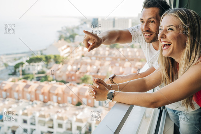 Happy couple looking out of window in coastal town