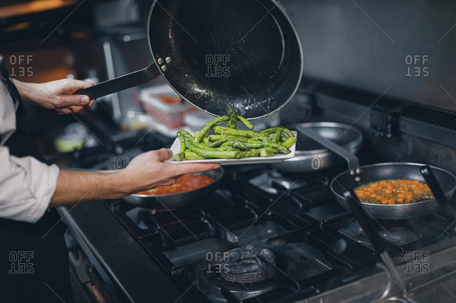 Chef preparing green asparagus dish in restaurant kitchen