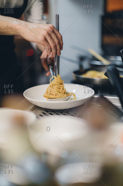Chef preparing a pasta dish in traditional Italian restaurant kitchen
