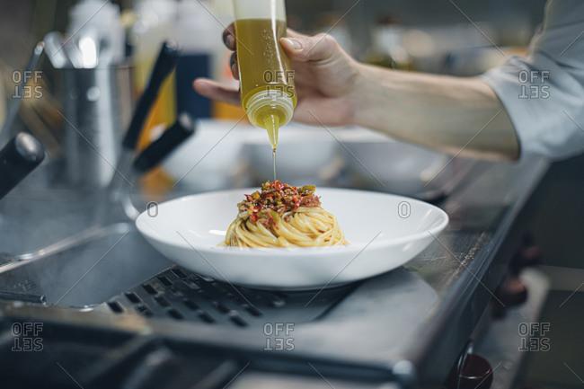 Chef preparing a dish in traditional Italian restaurant kitchen