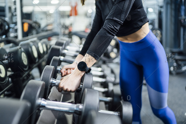 Close-up of woman taking dumbbells from rack in gym