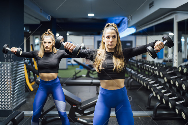 Twin sisters exercising with dumbbells in gym