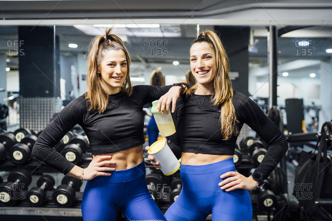Portrait of smiling twin sisters in gym