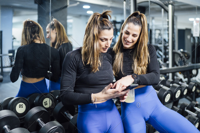 Twin sisters having a break in gym using smartphone