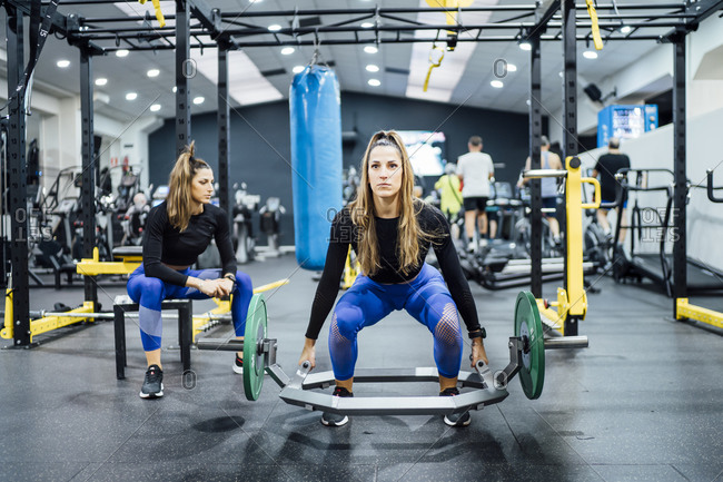 Woman exercising in gym with twin sister having a break
