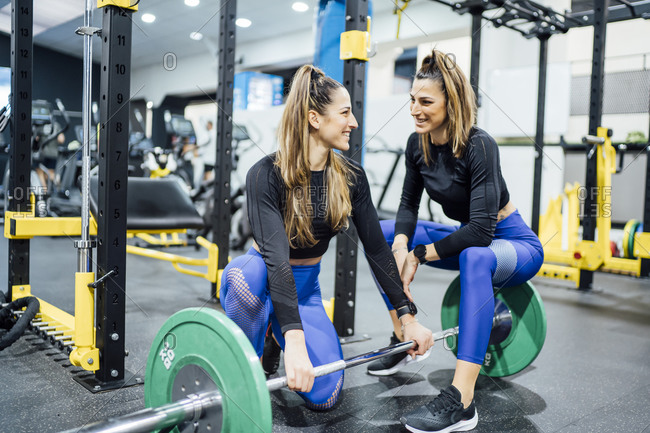 Smiling twin sisters with barbell in gym