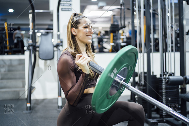 Smiling woman exercising with barbell in gym