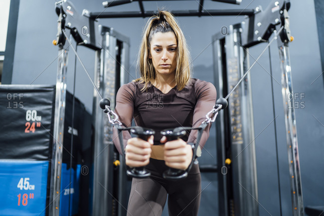 Woman exercising at cable machine in gym