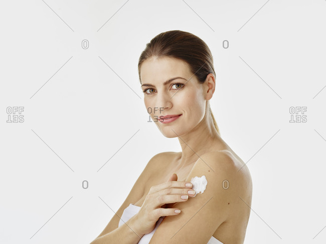 Portrait of smiling woman applying body cream on her arm