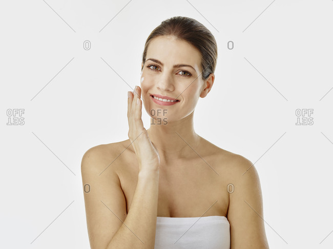 Portrait of smiling woman applying moisturizer on her face