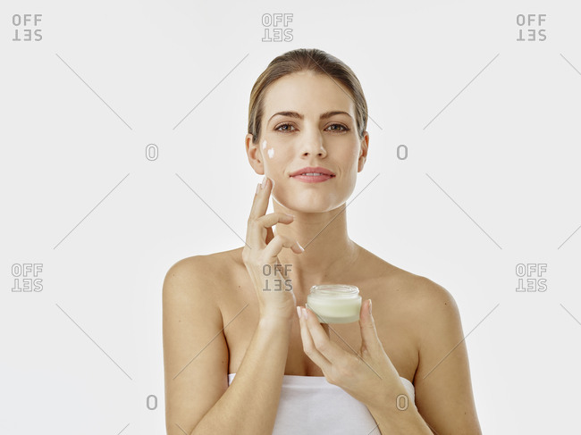 Portrait of smiling woman with cream pot applying moisturizer on her face
