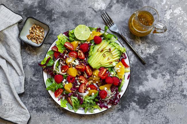 Studio shot of fruity salad plate with lambs lettuce- radicchio- lettuce hearts- avocado- tomato- pine nuts- raspberries- oranges- lime