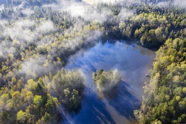 Germany- Bavaria- Geretsried- Aerial view of fog shrouding Birkensee lake and surrounding forest
