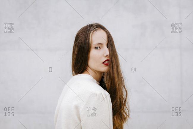 Portrait of young woman with long hair and red lips
