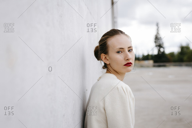 Portrait of serious young woman with red lips leaning against wall