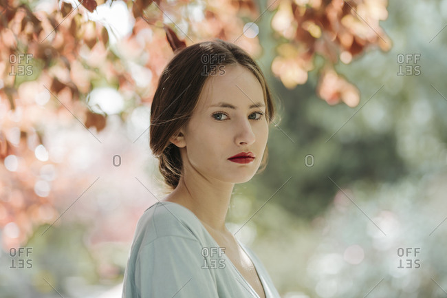 Portrait of young woman with red lips in nature