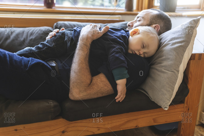 Father and son sleeping together on the sofa