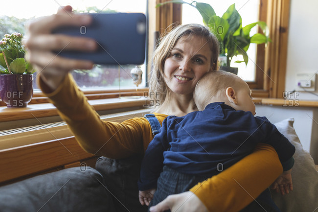 Woman taking a selfie with her cute sleeping son on the sofa
