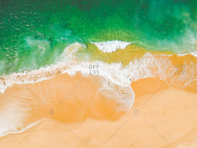 Aerial Drone Shot of ocean and sandy beach Green Turquoise